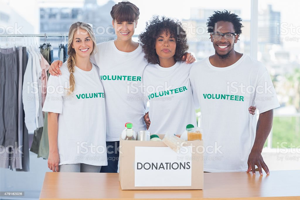 Volunteers standing in front of a donation box stock photo