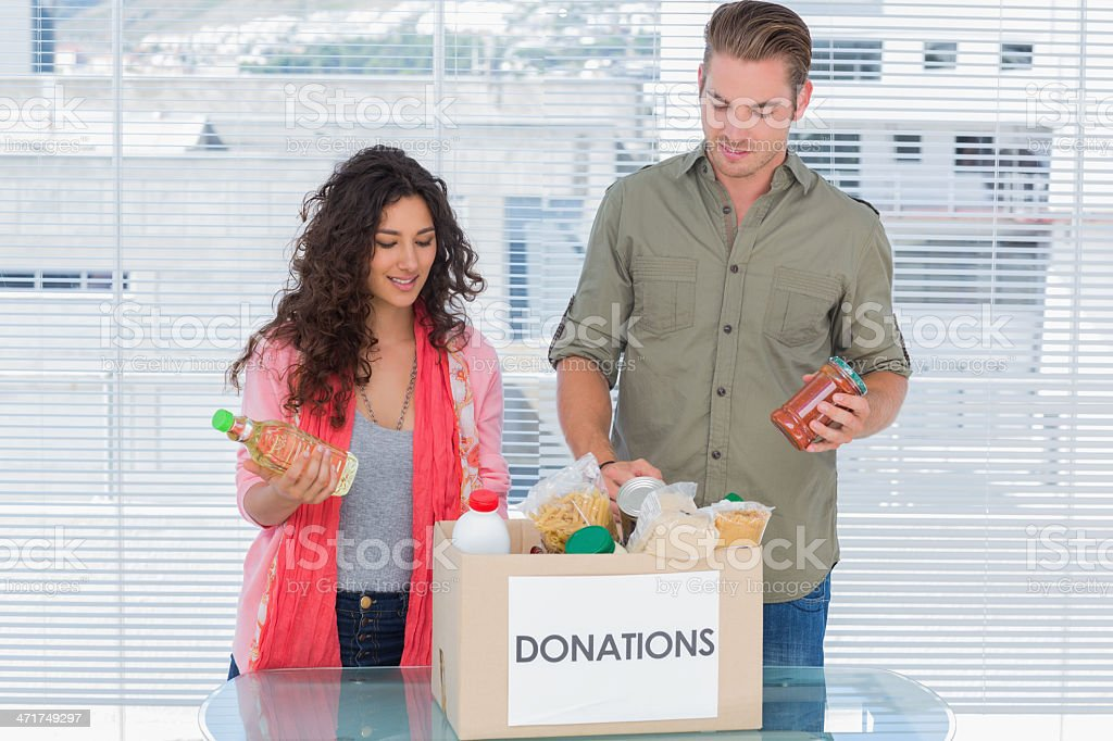 Volunteers taking out food from donations box stock photo