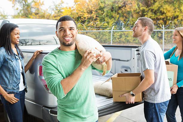 voluntários descarga doações de alimentos de fora do banco alimentar - charity and relief work - fotografias e filmes do acervo