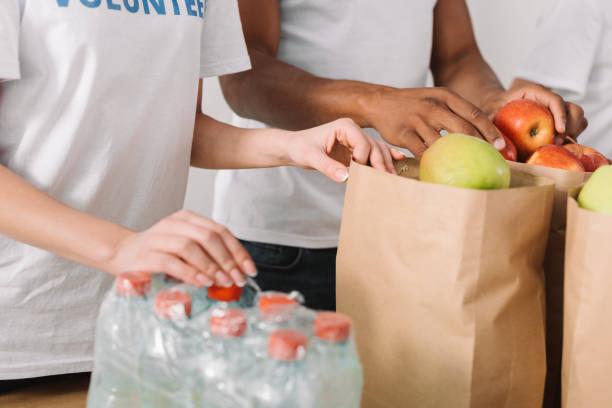 volunteers with charity goods - cassetta per le offerte foto e immagini stock