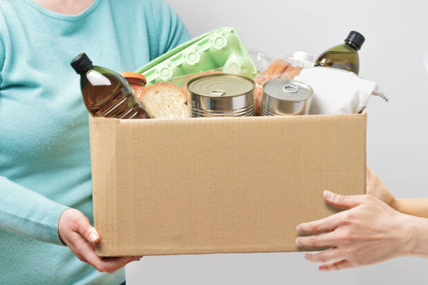 Volunteers with donation box with foodstuffs stock photo