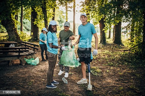 istock Volunteers with garbage bags cleaning in public park 1193309276