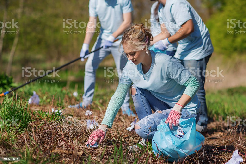 volunteers with garbage bags cleaning park area volunteering, charity, cleaning, people and ecology concept - group of happy volunteers with garbage bags cleaning area in park Adult Stock Photo