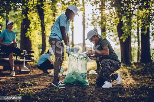 istock Volunteers with garbage bags in public park 1052205166