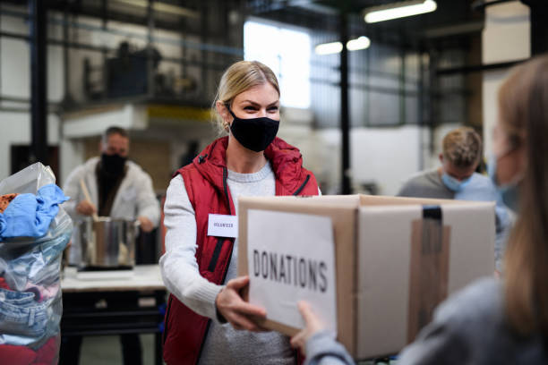Volunteers working with food and clothes in community charity donations center, coronavirus concept. stock photo