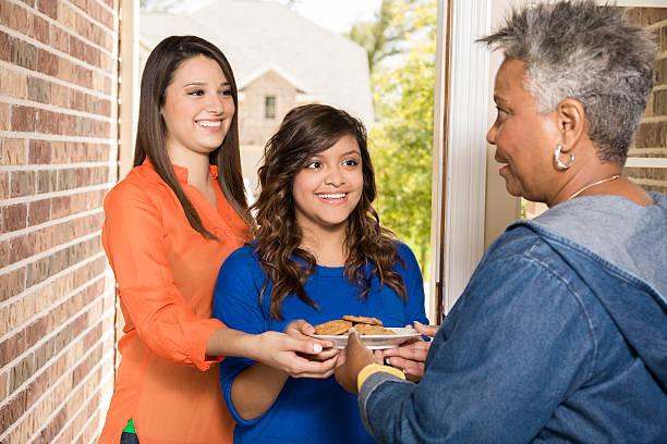 volontari: giovani adulti con i cookie per donna anziana a casa. - vicino foto e immagini stock