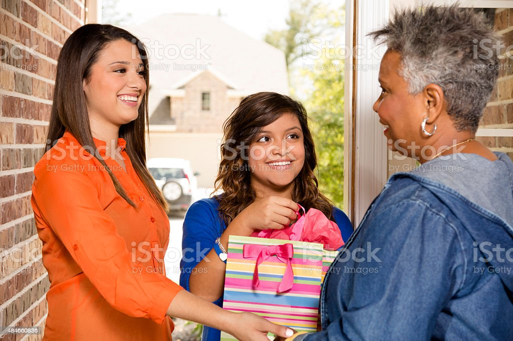 Volunteers:  Young adults bring gift to senior woman at home. stock photo