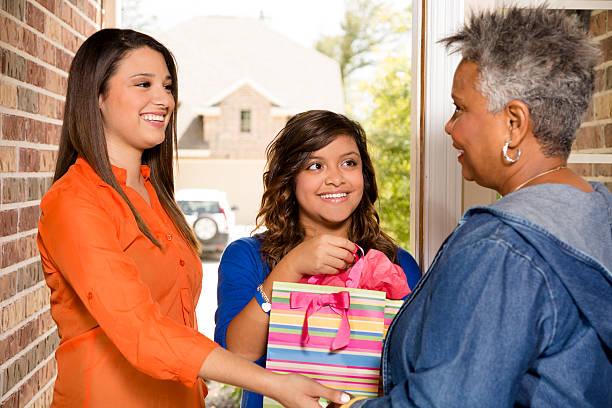 freiwillige: junge erwachsene mit geschenk senior frau zu hause fühlen. - jugendliche geburtstag geschenke stock-fotos und bilder