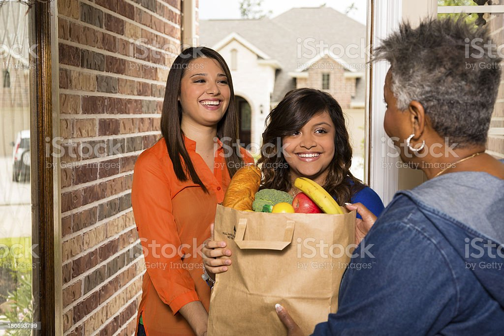 Volunteers:  Young adults bring groceries to senior woman. stock photo