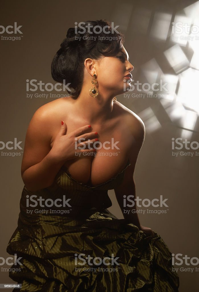 Voluptuous Woman in Formal Dress with Hand on Her Chest royalty-free stock photo