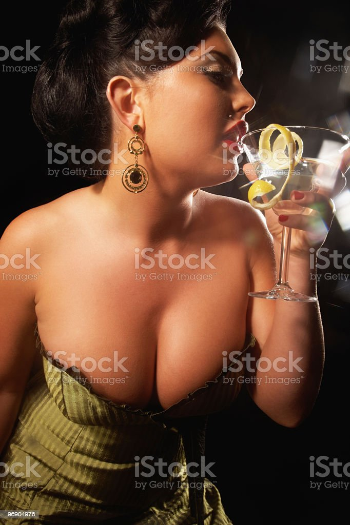 Voluptuous woman in formalwear drinking an alcoholic beverage royalty-free stock photo