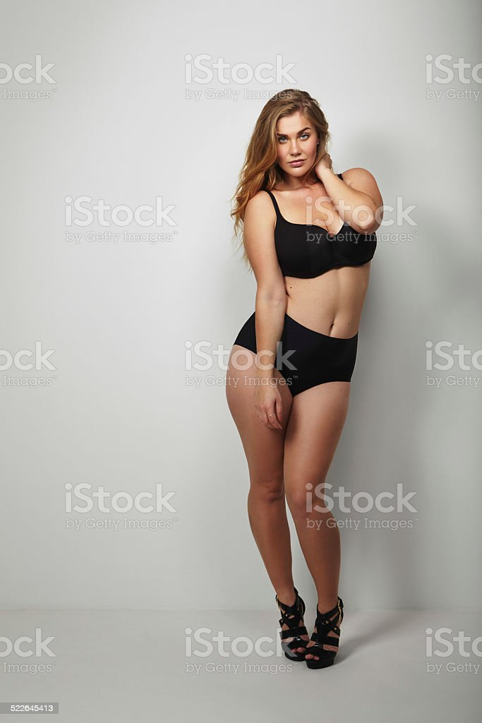 Voluptuous young woman posing sensually in bikini stock photo