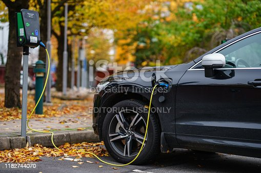Gothenburg, Sweden - October 21, 2019: Volvo car is plugged in for charging on street parking lot with beautiful autumn view background
