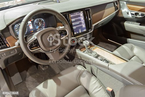 Brussels, Belgium - January 13, 2017: Interior and dashboard on a Volvo V90 luxury estate car. The Volvo V90 is available as stationwagon and as executive sedan, called S90. The V90 is equipped with a large touch screen and electronic dashboard screen. The car is fitted with leather seats and wood details.