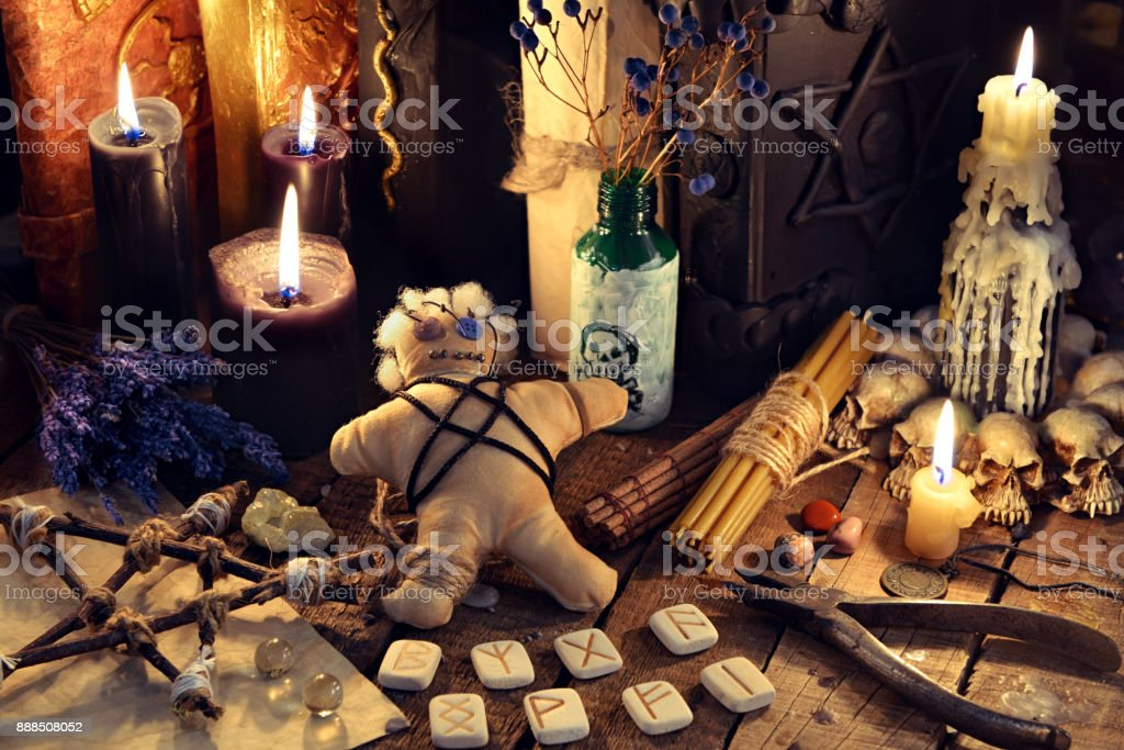 Voodoo doll, black candles, pentagram and old books on witch table stock photo
