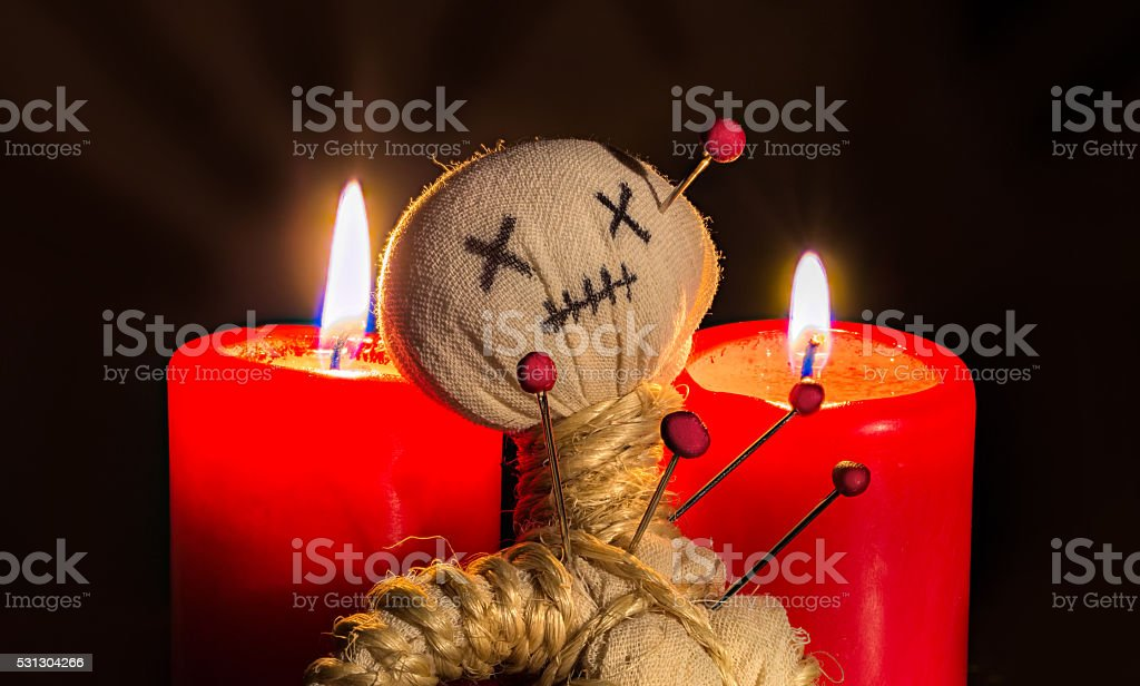 voodoo doll sitting between two candles stock photo
