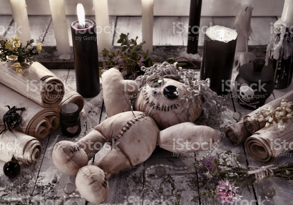 Voodoo doll with black candles and ancient scrolls stock photo