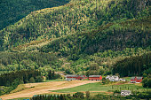 Voss, Norway. Summer Scenic Landscape With Fields And Red Farm Buildings. Traditional Norwegian Hillside Village With Old Wooden Houses.