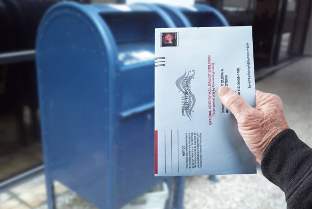Vote by mail: Person mailing absentee ballot for voting stock photo