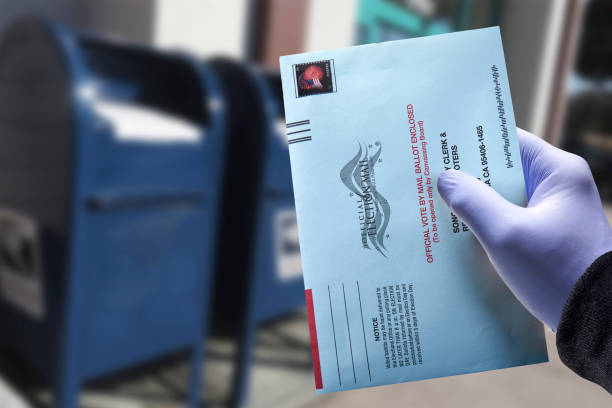 Vote by mail with glove: Person mailing absentee ballot wearing a protective surgical glove for voting stock photo