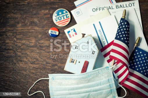 Vote from Home Absentee Ballot, protective face mask and campaign buttons on a wood surface. Concept