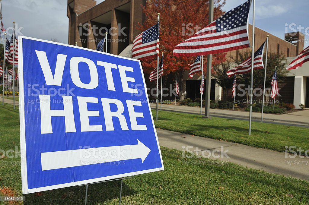 Vote Here Sign with American Flags in Background stock photo