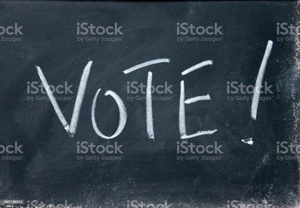 vote title written with chalk on blackboard stock photo