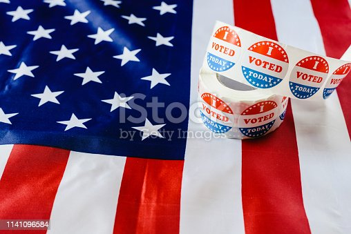 1157022917 istock photo I vote today stickers roll, in US elections on American flag. 1141096584