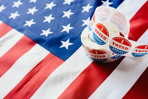 istock I vote today stickers roll, in US elections on American flag. 1157022917