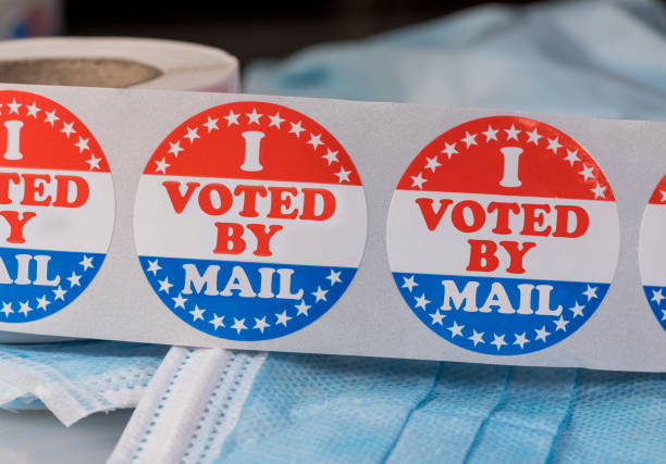 I Voted by Mail paper sticker on medical face mask to illustrate voting by mail in election stock photo