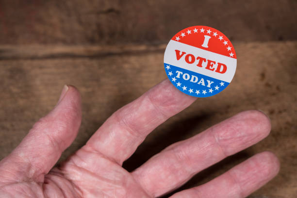 I Voted Today paper sticker on mans finger on rustic wooden table I Voted Today sticker on senior caucasian mans finger on rustic rural wooden table citizenship stock pictures, royalty-free photos & images