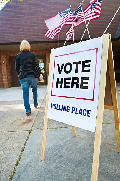 voter entering us polling place for voting vertical - vote sign stock photos and pictures