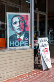 Charlottesville, Virginia, USA - June 7, 2012: An image of Barack Obama sits in a window. The hands of a woman operating a voter registration drive are visible behind the sign that reads \