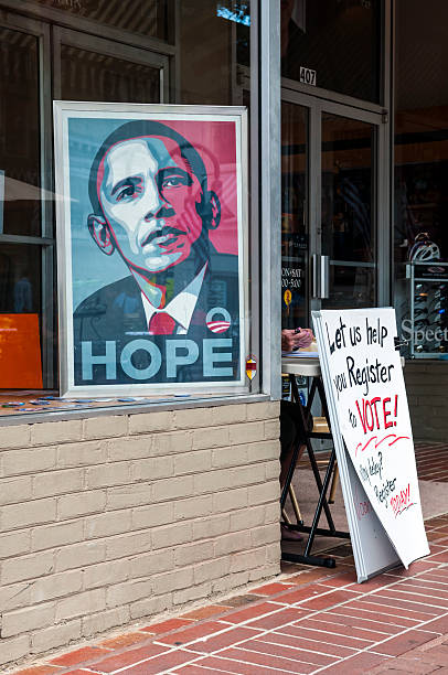 """Voter registration drive in Virginia Charlottesville, Virginia, USA - June 7, 2012: An image of Barack Obama sits in a window. The hands of a woman operating a voter registration drive are visible behind the sign that reads """"""""Let us help you Register to Vote!"""""""" barack obama stock pictures, royalty-free photos & images"""