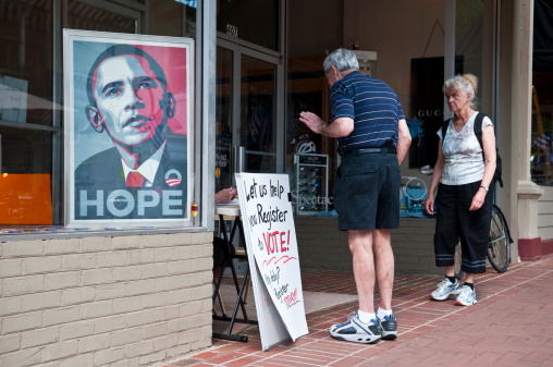 Charlottesville, Virginia, USA - June 7, 2012: An image of Barack Obama sits in a window beside two people, a man and woman, who are talking to a person registering voters. The sign says \