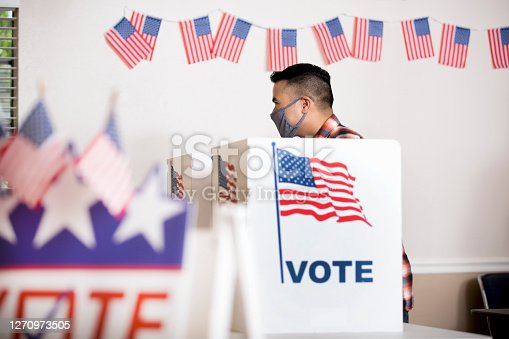 istock Voters placing their ballots.  Wearing face masks. 1270973505