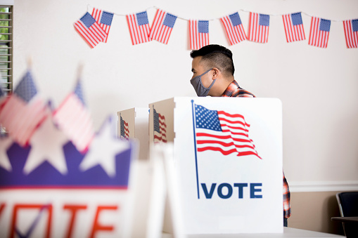 Voters wear protective face masks.  Asian voter at the ballot box casting his vote.
