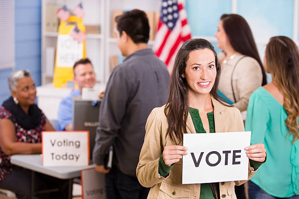 voters register, voting in usa elections. woman holds 'vote' sign. - vote sign stock photos and pictures