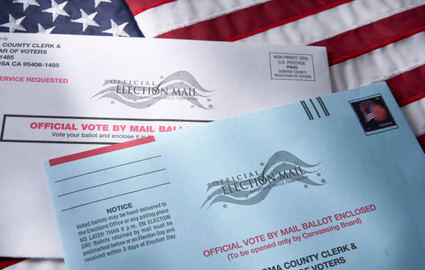 Voting ballot: Absentee voting by mail with ballot envelope on USA flag stock photo