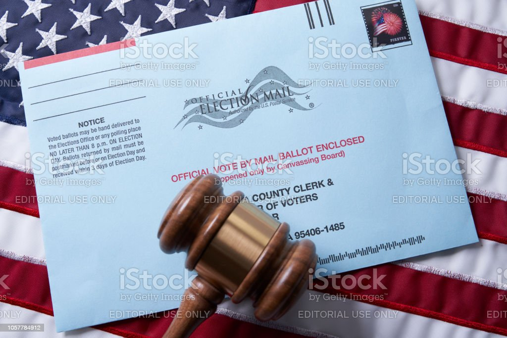 Voting ballot: Absentee voting by mail with ballot envelope on USA flag and gavel stock photo