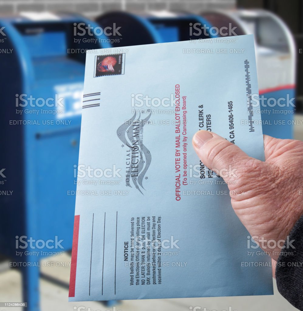 Voting ballot: Absentee voting by mail with hand holding envelope by mailboxes stock photo