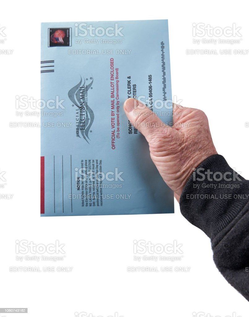 Voting ballot: Absentee voting by mail with hand holding envelope on white background stock photo