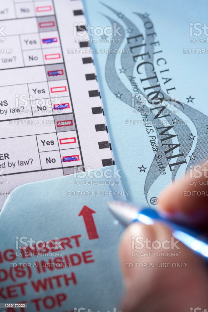 Voting ballot: Absentee voting by mail with man filling in choice for election and approval of measures stock photo
