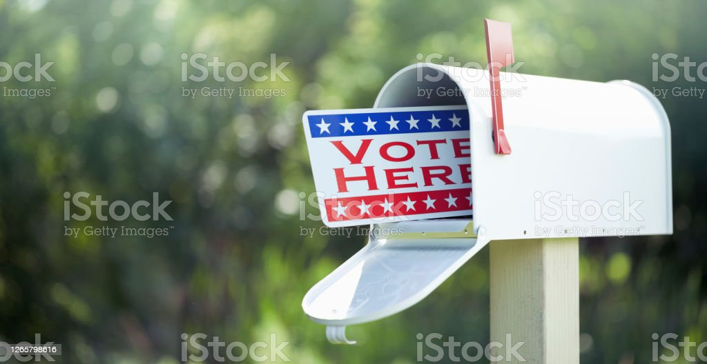 Voting By Mail Concept Voting by mail concept. Metal vote by mail signage in a mailbox against a defocused nature background. Backgrounds Stock Photo