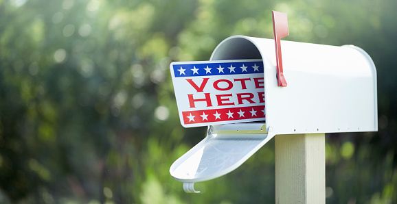 Voting by mail concept. Metal vote by mail signage in a mailbox against a defocused nature background.