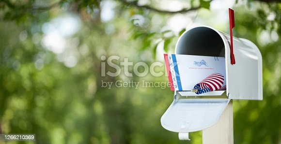 Voting by mail concept. Absentee ballot envelope in a mailbox against a defocused nature background.