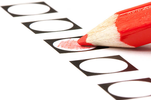 Voting form with red pencil filling in a black circle stock photo