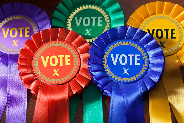 Voting in an Election Voting in a UK Election. Coloured Rosettes for the principal UK political parties political party stock pictures, royalty-free photos & images
