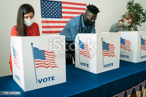People voting on voting booths, wearing face masks