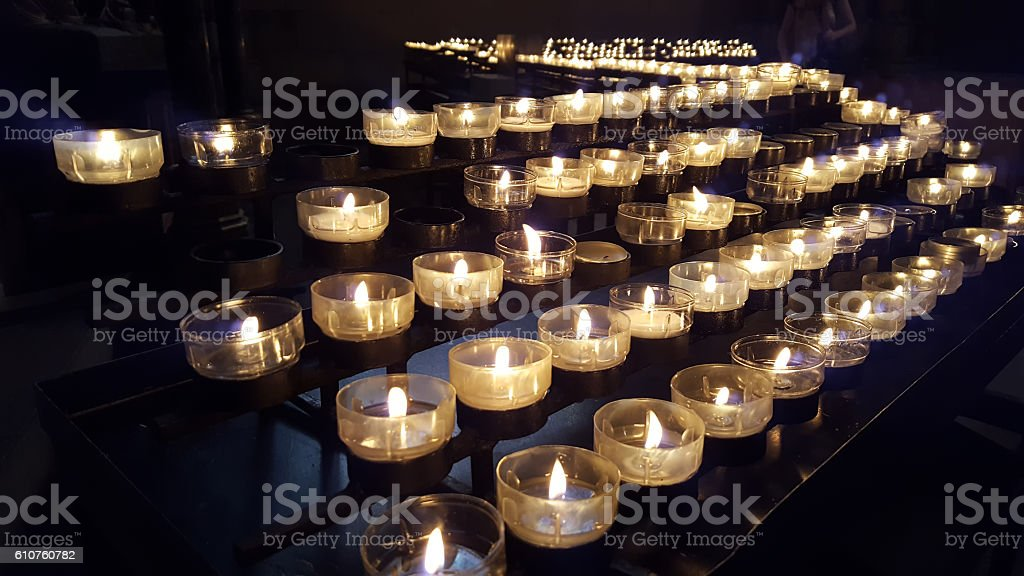 votive candles on a rack in a curch stock photo